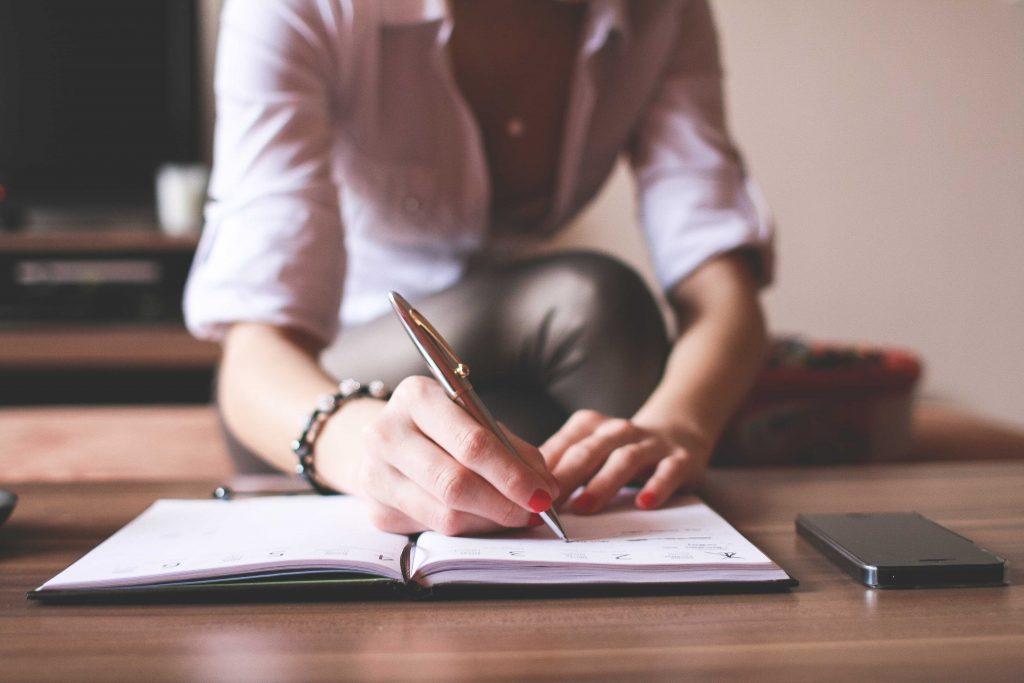 Пишет ручкой в тетради